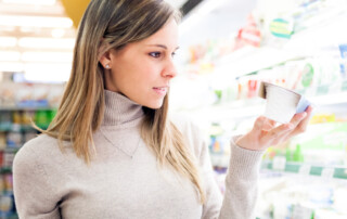 Young Blonde Woman Reading Nutrition Label